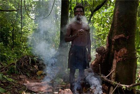 他们常年生活在深林里边,气候适宜,有时候很潮热,图片男子在抽部落烟